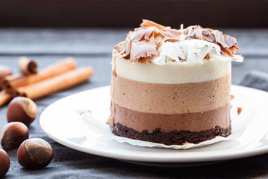 Mousse cake three chocolate, whole hazelnut and cinnamon sticks on a white plate. Dark wooden background