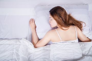 Woman sleeping on bed in bedroom
