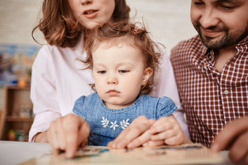 Portrait of cute little baby girl looking at pictures while reading book with her parents at home