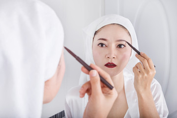 woman looking mirror and using pencil makeup eyebrow