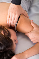 Sports massage. Massage therapist massaging shoulders of a female athlete, working with Trapezius muscle