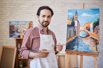 Portrait of talented professional artist working in art studio, posing and smiling to camera next to his paintings on easel
