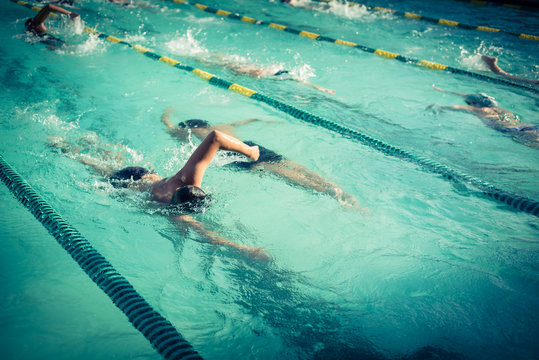 Close-up action shot of teen boy swimming front crawl stroke style in the blue water outdoor race pool. Focus on arm and water splash, some motion blurs. Swimming race and competition concept. Vintage