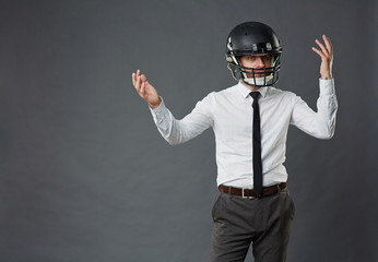 Portrait of confused middle-aged businessman wearing American football helmet making hopeless gesture against grey background, copy space to the left