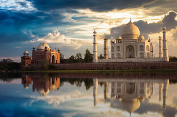 Fototapete - Taj Mahal with a moody sunset sky on the banks of river Yamuna. Taj Mahal is a white marble mausoleum designated as a UNESCO World heritage site at Agra, India.