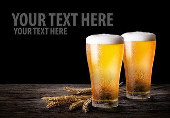 Cold beer with wheat on wooden table. Glasses of light beer on the isolate black  background with copy space.