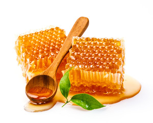 Honeycomb with honey spoon and leaf isolated on white background