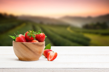 Red berry strawberry in a wooden bowl on the wooden table and the plantations background