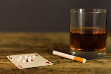 Addiction concept.Overhead shot of hard drugs and alcohol on wooden table.