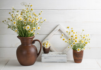 Daisy bouquet in clay jug with casket and photo frame