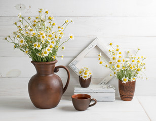 Daisy bouquet in clay jug with cup tea and photo frame on background of white wooden planks