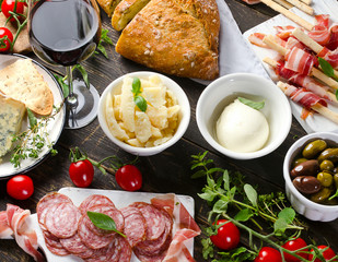 Different meat and cheese products with wine glass  on a dark wooden table