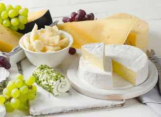 Wall Mural - Delicious cheese  with grapes on a wooden table