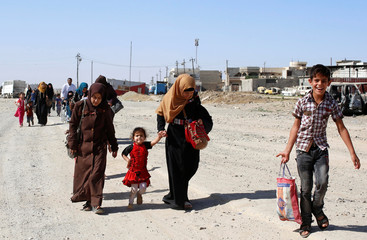 Residents who fled their homes due to fighting between Iraqi forces and Islamic State militants return to their village cleared by the Iraqi forces in western Mosul