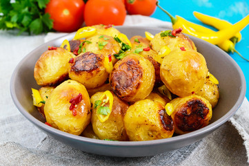 Baked potatoes with a golden crust with hot pepper, garlic, spices  and herbs in bowl.