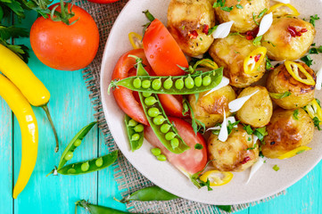 Spicy salad of baked potatoes, young garlic, tomatoes, green peas on a plate on a bright background. Top view. Close up