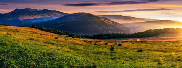 panorama of rural fields in foggy mountains at sunrise