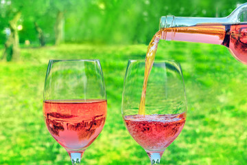 Rose wine poured from bottle into glasses at picnic