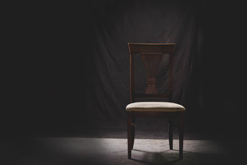 wooden chair in darkness in white tone