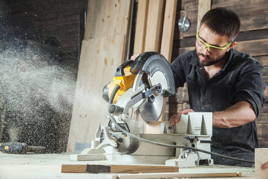 Close-up as a young male construction worker carpenter saws a circular saw blade, sawdust fly in the workshop