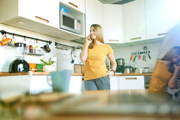 Young woman standing in a kitchen with mobile phone