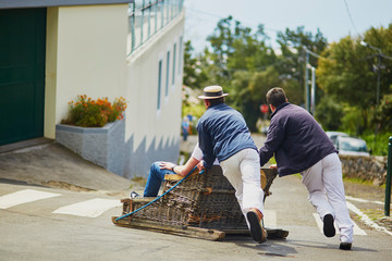 Toboggan riders moving cane sledge downhill on the streets of Funchal, Madeira island Fototapete