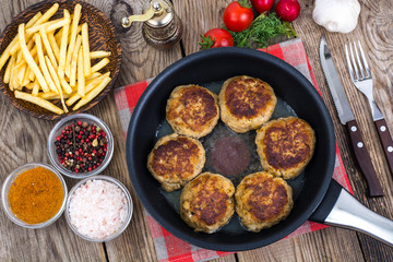 Fries on wooden plate and fried meat patties in frying pan