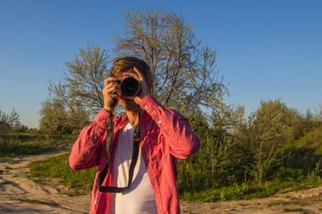 Man in pink shirt taking photo outdoor