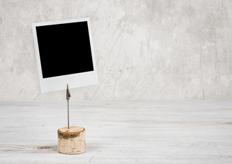 Empty mockup photo frame on wooden table against vintage wall