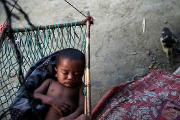 A boy sleeps in a hammock inside a  Rohingya refugee camp outside Kyaukpyu in Rakhine state, Myanmar