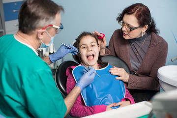 Young girl with mother on the first dental visit. Senior male dentist doing first check-up for patient at the dental office. Dentistry, medicine, stomatology and health care concept. Dental equipment