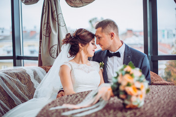 Cute married couple in cafe. Bride and groom in interior restaurant kiss each other.