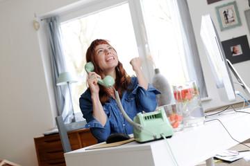 Frau mit roten Haaren und Pony  telefoniert mit einem alten Telefon und ist dabei emotional