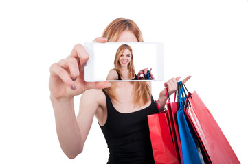 Portrait of young woman laughing with shopping bags