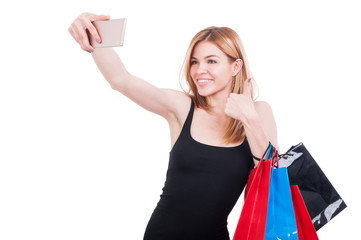 Pretty woman with smartphone and gift bags