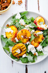 Fresh salad with grilled peach halves, arugula and burrata on a plate on white distressed wooden background. Top view. Summer food concept