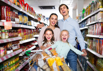 Couple with children buying food in hypermarket.