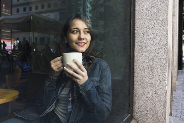View through window of inspired young woman having coffee sitting in cafe.
