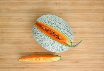 Top view partially cut cantaloupe melon on wood.