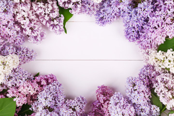 Spring white and violet lilac flowers on white wooden background. Bunch lilac arranged as frame with copyspace. Top view, flat lay.