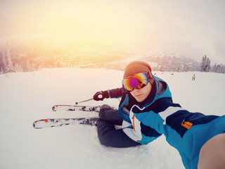 Guy sportsman goes on the normal skiing on the ski slope with the action camera. Sunset. Sheregesh, Kemerovo region, Russia.