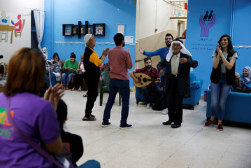 Volunteers join elderly in a party after the Iftar at the elderly care home during the Muslim holy month of Ramadan in Amman