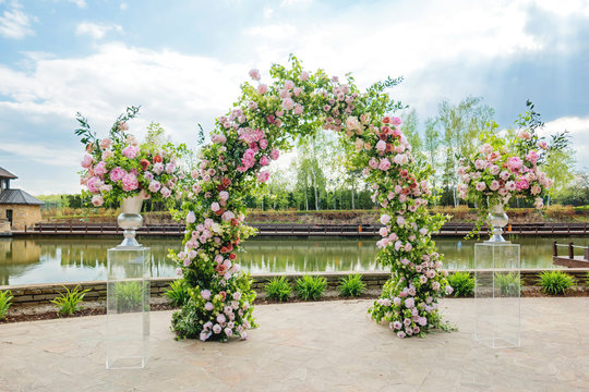 Beautiful floral arch for wedding ceremony. Vases with pink roses and peonies. Wedding set up outdoors in park near pond.