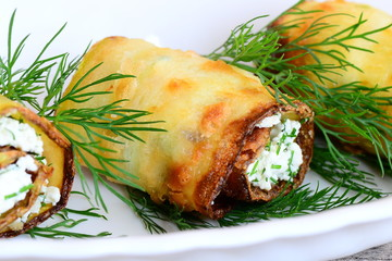 Photo sur Plexiglas Entree Rolls cooked from zucchini strips and stuffed with cottage cheese and dill. Fried zucchini rolls on a plate. Homemade beautiful starter recipe. Closeup