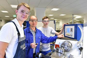 jugendliche Azubis und Ausbilder an einer CNC Drehmaschine - moderne Berufsausbildung im Handwerk // Young apprentices and trainers