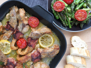 Fillets of carp roasted with bacon, garlic and lemon. Served with grilled vegetables - asparagus and tomatoes.