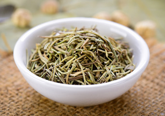 Dried rosemary leaves in a bowl