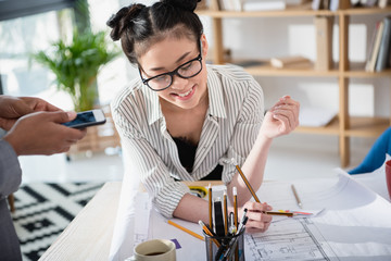 Smiling young asian businesswoman in eyeglasses working with blueprint in office