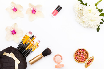Makeup brushes in black bag, flowers, Orchid and chrysanthemum, nail Polish and other cosmetics on a white background.