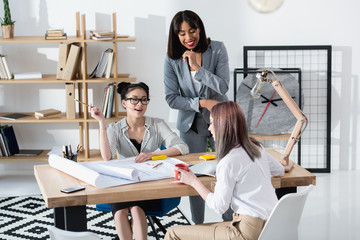 Smiling young businesswomen working together with blueprints in modern office